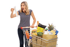 Shocked young woman looking at a store receipt Stock Images