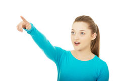 Shocked young woman pointing up. Royalty Free Stock Image