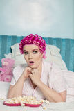 Shocked young woman with popcorn lying on bed while looking away Royalty Free Stock Photos