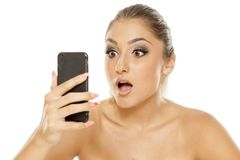 Shocked young woman. Looking at her phone on a white background royalty free stock photography