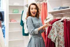 Shocked young woman shopper in blue dress in shop. Picture of shocked young woman shopper in blue dress in shop choosing clothes. Looking aside stock photography