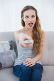 Shocked young woman sitting on sofa watching tv Stock Image