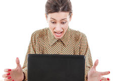 Shocked young woman sitting and using laptop royalty free stock images
