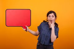 Shocked young woman with a speech bubble against a yellow background in studio. Surprised woman with thought bubble royalty free stock images