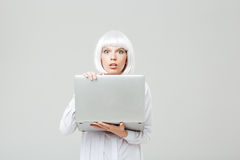 Shocked young woman standing and holding laptop. Over white background royalty free stock photo