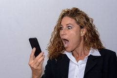 Shocked young woman staring at her mobile. With her mouth wide open as she reads a text message on the screen Royalty Free Stock Photography
