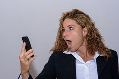 Shocked young woman staring at her mobile. With her mouth wide open as she reads a text message on the screen Royalty Free Stock Photo