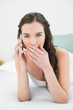 Shocked young woman using mobile phone in bed. Portrait of a shocked young woman using mobile phone in bed at home Royalty Free Stock Images
