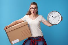 Shocked young woman with cardboard box showing clock on blue Royalty Free Stock Image