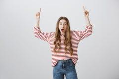 Shocking вещи случаясь вверх Изумленная и возбужденная привлекательная девушка указывая вверх с поднятыми руками, падая челюстью  Стоковые Изображения
