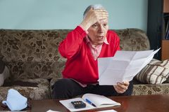 Shocking amount of bills an old lady has to pay for. Senior old woman shocked with the bills she receives, appalled and gasping royalty free stock image