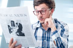 Shocking article. Portrait of man reading shocking article stock images