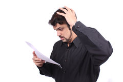 Shocking Bills. A young Indian man shocked looking at his high phone / power bills or invoices, on white studio background Royalty Free Stock Photography