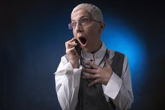 Shocking business news. Shocked and appalled senior business woman overreacting to some bad news she receives over her cell phone, blue background Royalty Free Stock Images