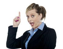 Shocking corporate woman pointing upwards Royalty Free Stock Photo