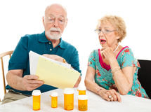 Shocking Cost of Medical Care. Senior couple shocked by the high cost of their medical bills.  White background Stock Image