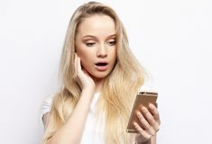 Shocking message. Surprised young blond hair woman holding mobile phone. And staring at it while standing against white background. Lifestyle concept Stock Photo