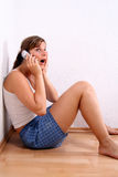 Shocking news. A young woman is chatting on the phone in her apartment Royalty Free Stock Photo