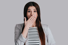 Shocking news!. Surprised beautiful young woman in smart casual wear covering mouth with hand and looking at camera while standing against grey background Royalty Free Stock Photography
