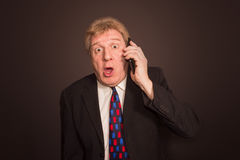 Shocking News. Surprised Mature Man In Suit With Mobile Phone Stock Photography