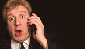 Shocking news. Surprised mature man in suit with mobile phone Stock Photos