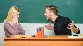 Shocking news. University or college students. Teacher and schoolmaster sitting at desk. Angry man and terrified woman. Shocking news. University or college stock photos