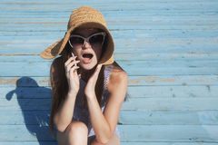 Shocking news!. Woman heards the shocking news by the phone on the vacation on the beach Stock Image