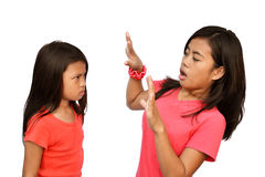 Shocking Reaction. Teenager shocked by the angry reaction of her little sister stock photo