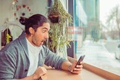 Shocking sms, news. Shocked man looking at phone stock image