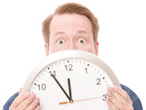Shocking time. Unrecognizable shocked man behind a clock - isolated on white, focus is on the eyes Stock Images