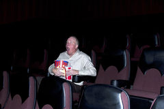 Shocking Twist. Man in empty, dark movie theater with a shocked expression on his face while holding popcorn and a soda royalty free stock photos