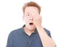 Shocking visual test. Young surprised man holding his one eye shut like you would do during a visit at the oculist - isolated on white Royalty Free Stock Photos