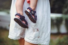 Shod feet of a child in the arms of a mother, a white dress, stained with shoes, raising children and loving them royalty free stock photography