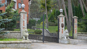 Shod gate and statues of lions at an entrance on the cottage territory Royalty Free Stock Photo