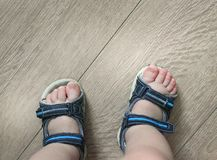 Shod legs of the baby. Children`s sandals on their feet. Toddler shoes. Tourist sandals for the smallest travelers. A new purchase royalty free stock image