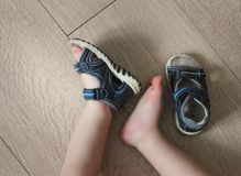 Shod legs of the baby. Children`s sandals on their feet. Toddler shoes. Tourist sandals for the smallest travelers. A new purchase stock photo