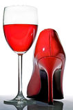Shoe. Close-up of elegant female red shoe and a glass goblet on a white background Royalty Free Stock Photography