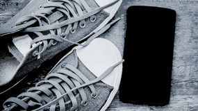 Shoe and black smartphone on wood floor. Abstract shoe and black smartphone on wood floor Royalty Free Stock Images