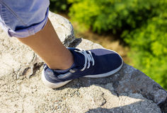 Shoe of a boy standing on the edge of a cliff in the mountains Royalty Free Stock Images