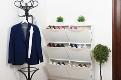 Shoe cabinet with footwear in room. royalty free stock photography