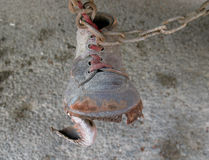 Shoe on Chain. An old, torn shoe hanging from a rusty metallic chain underneath a bus (a superstition in Lebanon to ward off the evil eye from cars, buses, six Royalty Free Stock Photo