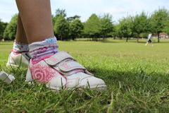 Shoe. A child's shoe at the park with a lovely background the trees. Just need a football Royalty Free Stock Photography