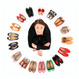 In the shoe circle. A picture of a pretty young woman sitting in the circle of shoes over white background Stock Photos