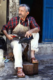 A shoe cobbler in Urfa bazaar in Turkey. A shoe cobbler repairs a shoe within the Urfa (Sanliurfa) Bazaar.  Many trades rarely seen in the western world still Royalty Free Stock Photography