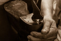 Shoe Cobbler Works with Hands. Closeup of cobbler working with old, worn tools to repair old, worn boot with strong, aged hands, in sepia stock photography