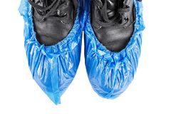 Shoe covers on shoes. Blue protective shoe covers on men`s shoes isolated on white background Royalty Free Stock Photography