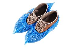 Shoe covers on shoes. Blue protective shoe covers on men`s shoes isolated on white background Stock Photography