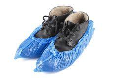 Shoe covers on shoes. Blue protective shoe covers on men`s shoes isolated on white background Stock Photo