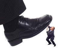 Shoe crushing a businessman. Businessman's foot stepping on tiny businessman-unequal competition concept stock images