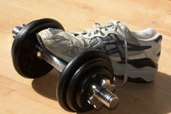 Shoe on dumbell. A sport shoe on a dumbell in the gym stock image